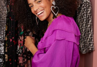Woman smiling and laughing in purple ruffle dress with silver heart earrings.