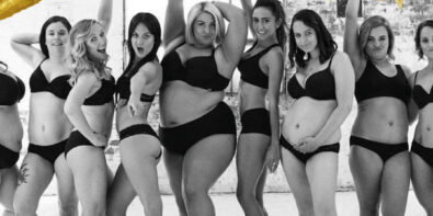 Women of all shapes and sizes standing together in black underwear smiling and laughing
