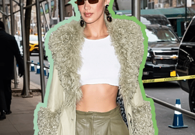Bella Hadid wearing a sage green coat with a faux fur trim walking down New York streets
